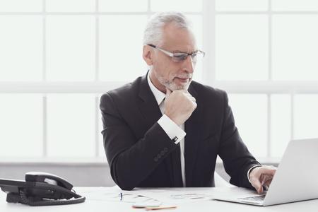 Volwassen zakenman die op Laptop in Office werkt. Professionele volwassen bebaarde werknemer zit aan Bureau en werkt op de computer. Succesvolle zakenman die kostuum op het werk draagt. Zakelijk levensstijlconcept Stockfoto - 107272205
