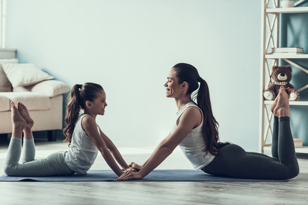 Young Woman and Little Girl Resting after Exercise. Beautiful Young Mother and Adorable Little Daughter Lying on Yoga mat. Mother and Daughter Together at Home. Healthy Lifestyle