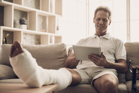 Man With Fractured Leg Sit On Sofa and Use Tablet. Handsome Caucasian Man Broken Leg in Plaster Cast Wearing White Clothes and Posing with Cheerful Expression. Rehabilitation and Health Care Concept