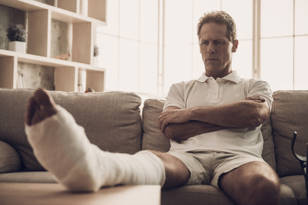Man With Fractured Leg Sit On Sofa Crossing Arms. Handsome Caucasian Person Feel Pain in Leg in Plaster Cast Posing with Upset Expression. Rehabilitation and Health Care Concept