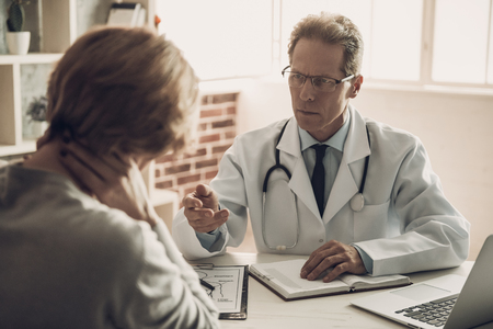 Serious Doctor Saying Diagnosis Female Patient. Doctor looking at Patient with Serious Expression. Confident Medical Worker Sitting at Table in Cabinet. Doctor's Appointment. Medical Issue Concept