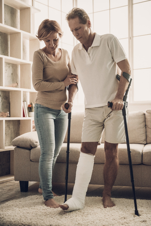 Beautiful Woman Help Husband to Move with Gypsum. Handsome Man with Broken Leg in Plaster Cast Move Along Room with Gypsum with Crutches. Wife Support. Rehabilitation and Health Care Concept