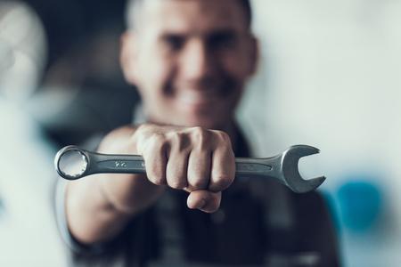 ぼやけた背景上のツールを備えた自動メカニック。ガレージで修理工強い拳保持メタリックレンチのクローズアップ。自動車修理サービスコンセプト自動車マスターコンセプト