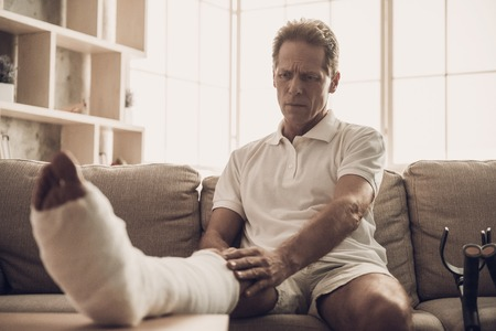 Portrait of Man With Fractured Leg Sitting On Sofa. Handsome Caucasian Man Wears White Clothes and Holds his Ankle Posing with Upset Expression. Rehabilitation and Health Care Concept