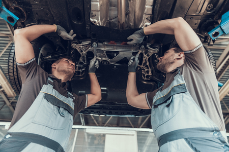 Auto Mechanics Working Underneath Lifted Car. Two Mid Adult Automobile Rapairmen Repairing Car in Workshop Wearing Comfortable Uniform. Technic occupation. Auto Service Concept