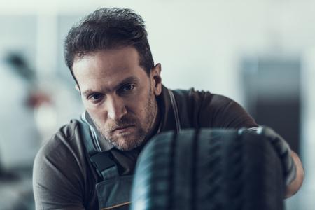 Handsome Auto Mechanic Cheking Car Wheel. Portrait of Caucasian Adult Machinist Doing Wearing Uniform Work in Garage. Technic occupation. Automobile Repair Service Concept. Standard-Bild - 107287107