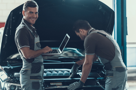 Two Car Mechanics Working in Auto Repair Service. Professional Caucasian Handsome Happy Workers in Uniform and Gloves Repairing Automobile with Opened Hood Using Laptop. Repair Service Concept.