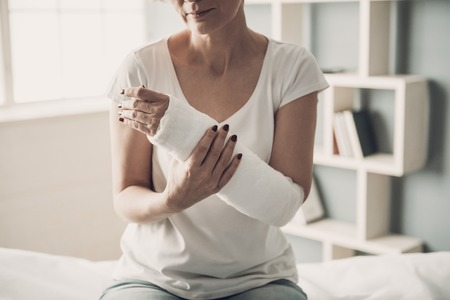 Close-up of Female Broken Arm in Plaster Cast. Caucasian Injured Woman in White T-Shirt Sitting and Holding Wrist in Gypsum Bandage with Physical Pain in Fractured Bone. Health Care concept