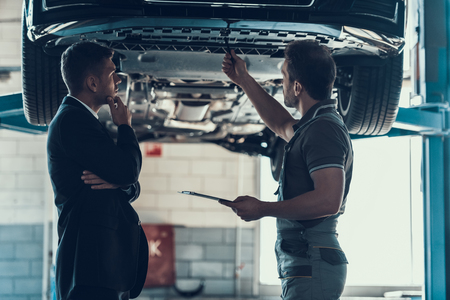 Auto Mechanic Showing Client Car Problem. Handsome Buisiness Man in Black Suit Listening Cause of Breakage. Automobile Master in Uniform Explainig in Garage. Repair Service Concept.