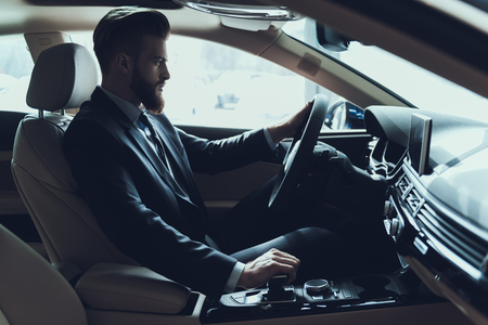 Business Man Driving Car Shifting Gear Stick. Stylish Confident Caucasian Person Wearing Black Suit Posing in Auto with Serious Expression. Driving Automobile with Automatic Gears Concept