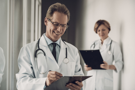 Arzt und Krankenschwester füllen die Krankengeschichte auf. Porträt von kaukasischen erfahrenen Medizin-attraktiven Arbeitern in der einheitlichen Diagnose, die im Krankenhaus steht. Gesundheitskonzept Standard-Bild