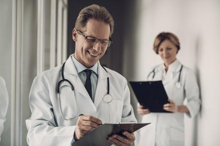 Médecin et infirmière remplissant les antécédents médicaux. Portrait de la médecine expérimentée du Caucase des travailleurs attrayants en uniforme faisant le diagnostic permanent à l'hôpital. Concept de soins de santé Banque d'images