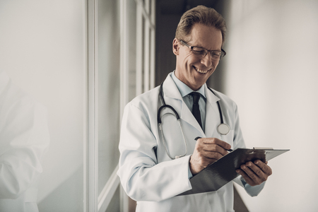 Portrait of Doctor Filling up Medical History. Happy Smiling Caucasian Experienced Physiotherapist Standing in Hospital Wearing White Lab Coat and Glasses and record diagnosis. Healthcare Concept