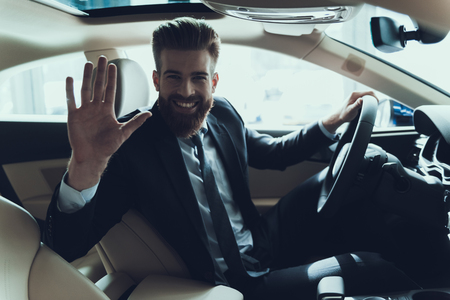Business Man Waving Hand while Driving Car. Stylish Caucasian Person Wearing Black Suit Show Hello Gesture Posing in Auto with Cheerful Expression. Driving Automobile with Automatic Gears Concept