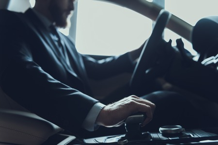 Close-up Of Male Hand Change Gear and Driving Car. Caucasian Person Wearing Black Suit Posing in Auto Using Car Transmission. Driving Automobile with Automatic Gears Concept Stock Photo