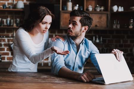 Verrast vrouw bespioneren man met laptop. Vrouw betrapt echtgenoot die pornografische video's bekijkt op laptop of sms't met Meesteres. Family Ruzie. Concept van familieconflict.