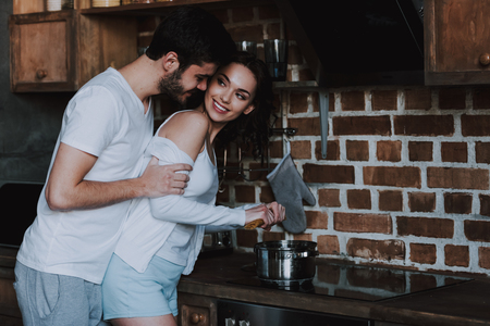 Young Lovers Smiling and Hugging Before Having Sex. Handsome Couple in Love Hugging in Kitchen. Love Concept. Romantic Date. Relationship. Husband and Wife.