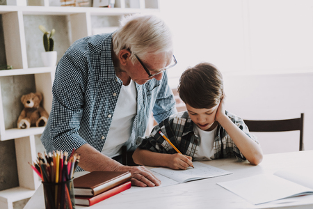 Grandson Doing School Homework with Old Man Home. Family Relationship Between Grandfather and Grandson. Grandpa Teaching, Male Grandchild, Learning Concept. Relations and People Concept. 写真素材