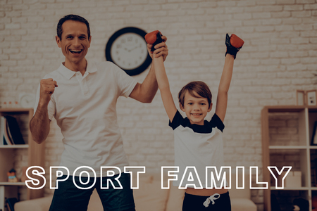 Father Is Lifting Up Sons Hand. Victory Concept. Father And Son Boxing Training. Sports Family. Healthy Lifestyle. Active Holiday. Young Winner. Working Out At Home. Kid With Fight Gloves. Reklamní fotografie