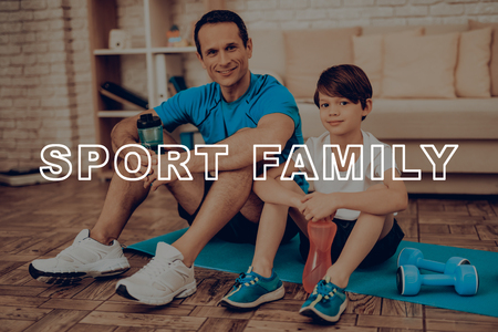Father And Son Are Resting On The Gym Carpet. Healthy Lifestyle. Active Holiday. Sports Clothes. Working Out At Home. Bottles Of Water. Body Exercises. Family Training Day Concept.