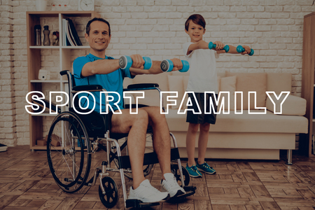 Man In A Wheelchair With Son Are Doing Exercises With Dumpbells. Healthy Lifestyle. Active Holiday. Sports Clothes. Working Out At Home. Gym Carpet. Repeat Practice. Body Exercises. Reklamní fotografie