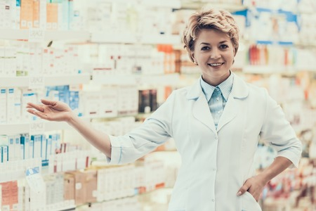 Portrait of Mature Smiling Pharmacist in Drugstore. Adult Female Farmacist wearing White Coat pointing on Shelfs full of Drugs on Background in Pharmacy. Pharmacist Working in Drugstore