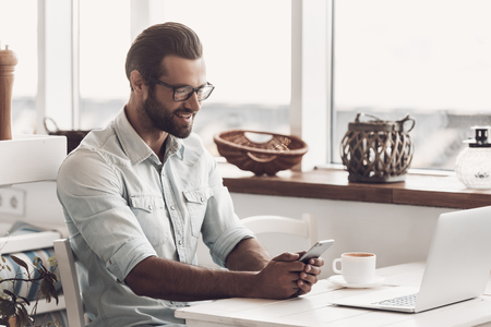 Young Smiling Man Working on Laptop in Cafe. Happy Handsome Bearded Business Man Sitting at Table and Using Smartphone next to Laptop. Confident Smiling Businessman Working Remotely 版權商用圖片