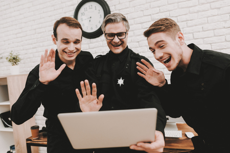 Smiling Police Officers Are Staring On Laptop. Saying Hello. Crime Fighters. Detective Uniform. Working Together. Citizens Protection. Public Order. Relaxing Concept. Having A Break. Stock fotó