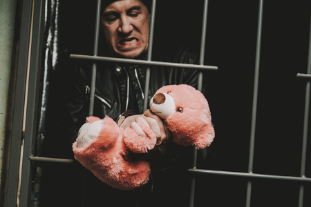A Man In Handcuffs Is Behind Bars In A Police Station. Jailed Suspect. Bandit In Leather Jacket. Successful Arrest. Commit A Crime. Guilt Negation. Close-up Criminal. Plush Toy Holding. Stock Photo