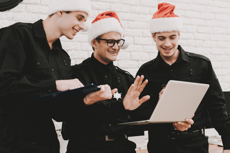 Smiling Officers In A Santa Claus Caps Staring On Laptop. Crime Fighters. National Duty. Professional Consulting. Detective Uniform. Citizens Protection. Working Together. Saying Hello. Stock fotó