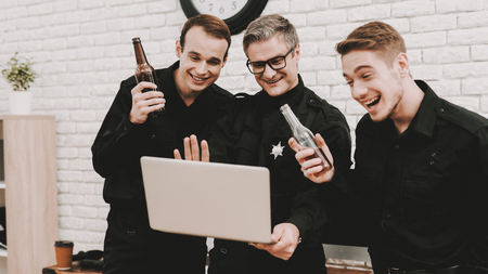 Smiling Police Officers Are Staring On Laptop. Saying Cheers. Bottle Of Alcohol. Crime Fighters. Detective Uniform. Working Together. Citizens Protection. Relaxing Concept. Having A Break.