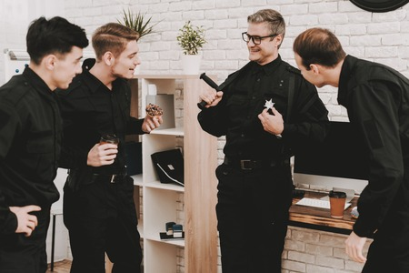 Smiling Officers In Department Office. Relaxing Concept. Coffee Break. Tasty Donuts. Working Together. Citizens Protection. Public Order. Phone Talking. Handscuffs On Table. Detective Uniform.