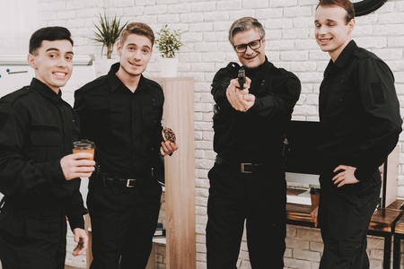 Smiling Officers In Department Office. Relaxing Concept. Coffee Break. Tasty Donuts. Working With A Gun. Citizens Protection. Public Order. Phone Talking. Handscuffs On Table. Detective Uniform. Stock fotó