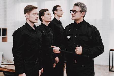 Adult Officer Instructs Subordinates In Police Station. Arrest Teaching. Work Together. Crime Fighters. Ask A Question. Professional Consulting. Cop's Uniform. Citizen's Protection. Stok Fotoğraf
