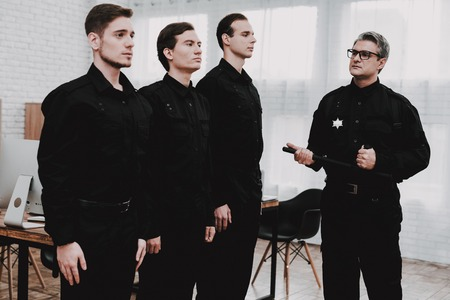 Adult Officer Instructs Subordinates In Police Station. Arrest Teaching. Work Together. Crime Fighters. Ask A Question. Professional Consulting. Cops Uniform. Citizens Protection. Stock fotó