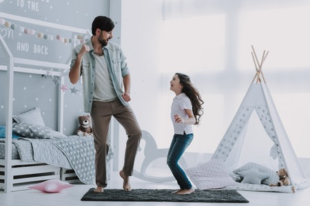 Handsome Young Father Dancing with Little Girl. Happy Fathers Day Concept. Father with Daughter Spending Time Togetherness at Home. Happy Family Daughter Laughs on Holiday