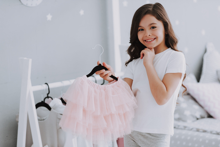 Little Cute Girl Choosing a Dress in Bedroom. Pretty Little Happy Girl Sneaking Among Clothes in Wardrobe. Dress Up Clothes Hanging on a Clothesline for Imagination or Creativity Concept.