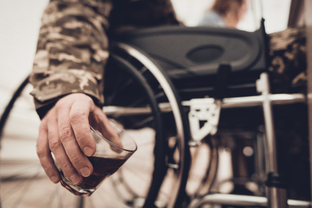 A Veteran In A Wheelchair Sitting With Glass Of Whiskey. Meeting Concept. Family Background. Camouflage Uniform. Drink Alcohol. Patriotic Comeback. Paralyzed Soldier. Depression Problem. Banque d'images - 107721837