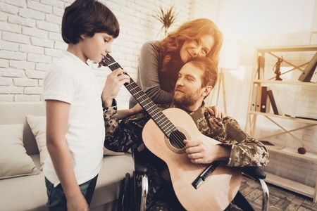 Veteran In The Wheelchair Guitar Play Concept. Family Meeting. Son And Wife. Camouflage Uniform. Family Background. Resting Together. Feelings Showing. Patriotic Comeback. Paralyzed Soldier. Banque d'images - 107792160