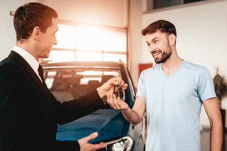 Showroom Dealer The Gives Car Keys To The Buyer. Dialogue With A Dealer. Cheerful Customer. Automobile Salon. Make A Decision. End Of A Deal. Good Offer. New Buying. Business Trade. Zdjęcie Seryjne