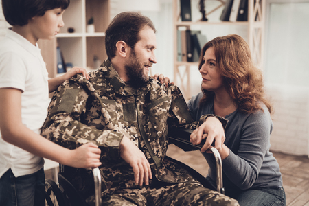 Male Veteran In Wheelchair Homecoming Concept. Home Meeting. Son And Wife. Embrace With Family. Camouflage Uniform. Child Hanging. Heroic Comeback. Paralyzed Soldier. Disabled Man.