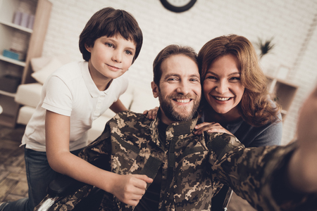 Disabled Man In A Wheelchair Makes A Selfie With Family. Meeting After War. Son And Wife. Camouflage Uniform. Feelings Showing. Return From Army. Paralyzed Soldier. Homecoming Concept. Stok Fotoğraf - 107734782