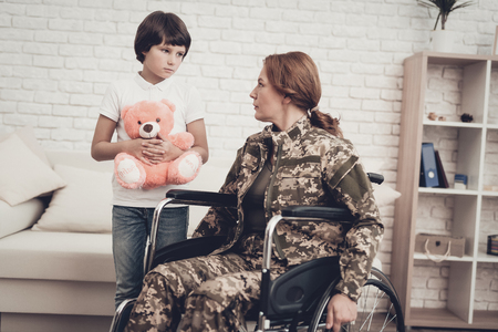 Woman Veteran In Wheelchair Homecoming Concept. Family Meeting. Leaving From War. Fluffy Toy. Camouflage Uniform. Son Hanging. Feelings Showing. Patriotic Comeback. Paralyzed Soldier. Banque d'images - 107862454