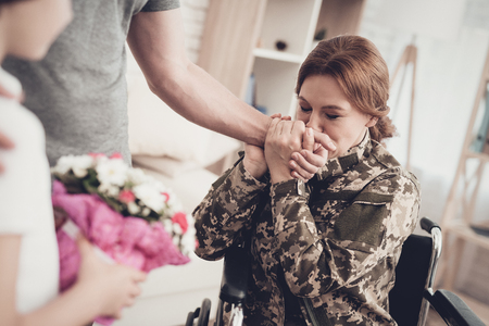 Woman Veteran In Wheelchair Homecoming Concept. Family Meeting. Son And Husband. Embrace With Mother. Camouflage Uniform. Child Hanging. Flowers Bouquet. Patriotic Comeback. Paralyzed Soldier.