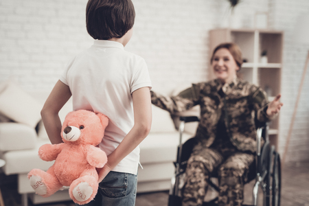 Woman Veteran In Wheelchair Homecoming Concept. Family Meeting. Leaving From War. Fluffy Toy. Camouflage Uniform. Son Hanging. Feelings Showing. Patriotic Comeback. Paralyzed Soldier.