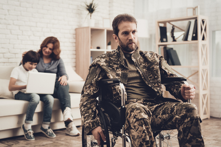 Disabled Soldier In Wheelchair. Suffering From Pain. Meeting After War. Son And Wife Background. Camouflage Uniform. Family Concept. Paralyzed Hero. Home Leisure. Return From Army. Banque d'images - 107792176