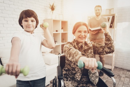 Disabled Woman In A Wheelchair. Dumpbells Exercises With A Son. Meeting After War. Camouflage Uniform. Paralyzed Soldier. Homecoming Concept. Return From Army. Healthy Lifestyle. Mother And Child. Banque d'images