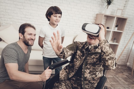 Disabled Woman Soldier Family Are Having Fun. Meeting After War. Son And Husband. Camouflage Uniform. Virtual Reality Glasses. Paralyzed Soldier. Homecoming Concept. Return From Army. Banque d'images - 107752737