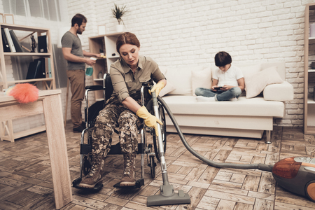 Female Veteran In A Wheelchair Is Cleaning House. Supporting Husband. Camouflage Uniform. Disabled Soldier. Vacuum Cleaner. Working Together. Holiday Leisure. Yellow Gloves. Free Time.