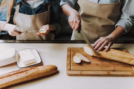 Close up Of Senior Woman Hands Cutting Baguette. Granddaughter Hands Holding Knife with Butter. Making Sandwich. Grandma and Granddaughter Cooking Food. Healthy Lifestyle. Cooking At Home. Banque d'images